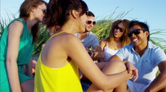 Multi ethnic males and females enjoying beach party with guitar on sand dunes Arkistovideo