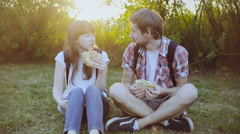 Couple eating sandwich and talking outdoor in nature Stock Footage