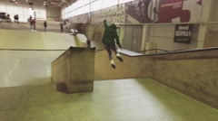 Roller skater in green hoody make jump, grab feet in air. Extreme hobby Stock Footage