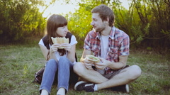 Couple eating sandwich and talking outdoor in nature at sunset Stock Footage