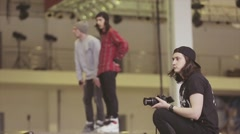 Cameraman in hat, roller skaters prepare on springboard. Competition in Stock Footage