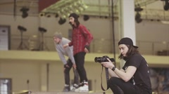 Cameraman in hat shoot, roller skaters jump out springboard. Competition in Stock Footage