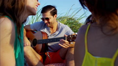 Multi ethnic friends chilling and playing the guitar at picnic on beach vacation Stock Footage