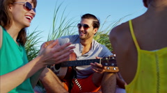 Happy multi ethnic people relaxing with picnic on ocean beach Stock Footage