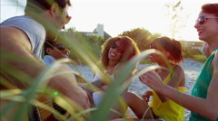 Multi ethnic males and females enjoying beach party with guitar on sand dunes Stock Footage
