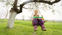 Little funny kid swinging on teeterboard Stock Footage