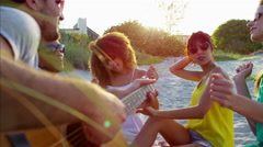 Multi ethnic males and females with guitar enjoying party on beach vacation Stock Footage