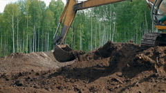 An excavator is digging the black soil near the forest Stock Footage