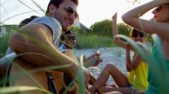 Caucasian American male playing the guitar and chilling on beach picnic Stock Footage