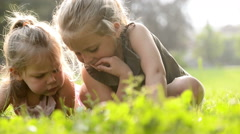 Happy blonde sisters lay down on grass are reading fairy tales on tablet Stock Footage