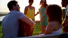 Multi ethnic people dancing and playing the guitar at party on beach at sunset Arkistovideo