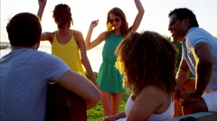 Multi ethnic people enjoying party with guitar and dancing on beach at sunset Stock Footage