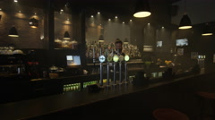 4K Cocktail barman juggling a bottle & setting up bar for opening time Stock Footage