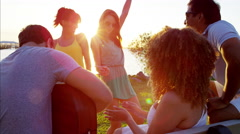 Happy multi ethnic males and females enjoying beach party with guitar at sunset Stock Footage
