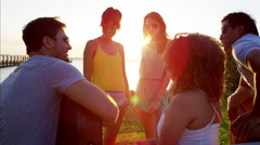 Multi ethnic males and females with guitar enjoying party on beach holiday Stock Footage