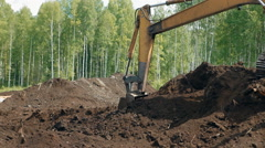 An excavator is loading the ground with a bucket Stock Footage
