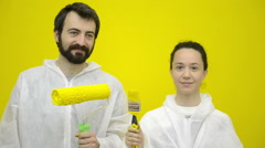 Young happy couple is gesturing with yellow brushes - stock footage