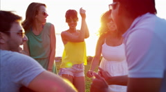 Multi ethnic people in casual clothing enjoying dance party on beach at sunset Stock Footage