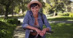 Happy smiling black woman leaning against handlebars on bike in park - stock photo