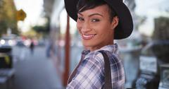 African American woman smiling on busy city street - stock photo
