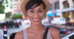 Happy smiling black woman holding hat on San Francisco city street Stock Photos