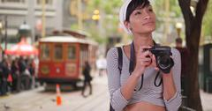 Woman with camera taking photo on San Francisco city street with trolley in b Stock Photos