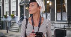 Woman with camera taking photo on Amsterdam city street Kuvituskuvat