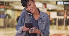 Woman talking on cellphone and holding passport in airport terminal while wai Stock Photos
