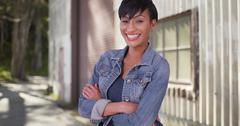 Confident millennial woman with arms crossed wearing jean jacket Stock Photos