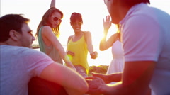 Caucasian American male playing the guitar and enjoying party on beach at sunset Stock Footage