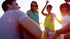 Multi ethnic males and females with guitar enjoying party on the beach Stock Footage