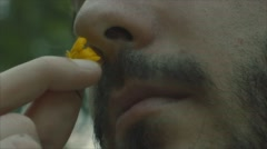 Young Adult Smelling a Yellow Flower - Super Close Up Stock Footage