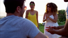 Young multi ethnic people playing the guitar at party on the beach at sunset Arkistovideo