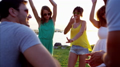 Multi ethnic people enjoying party and dancing on the beach at sunset Arkistovideo