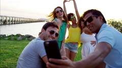 Multi ethnic people taking a photo on mobile on their beach holiday at sunset Stock Footage
