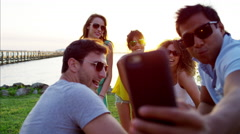 Multi ethnic people having fun taking a picture on the beach at sunset Stock Footage