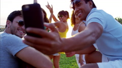 Multi ethnic college friends having fun taking a picture on the beach at sunset Stock Footage