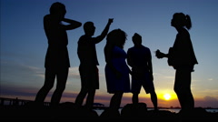 Silhouette of young people dancing on ocean beach at sunset Stock Footage