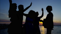 Silhouette of people dancing and playing the guitar on the beach party at sunset Stock Footage