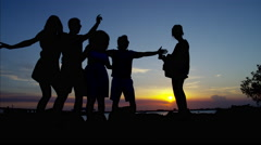 Silhouette of young friends dancing by the ocean at sunset Stock Footage