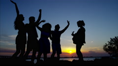 Silhouette of happy males and females enjoying sunset on their beach holiday Stock Footage