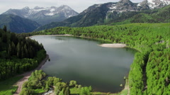 Aerial View of Lake Surrounded by Green Forest and Mountains Stock Footage
