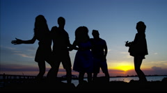 Silhouette of young friends dancing on ocean beach at sunset Stock Footage