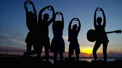 Silhouette of people making heart symbol with hand on beach party at sunset Stock Footage
