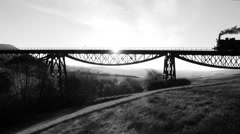 Black and white background of steam engine locomotive crossing bridge road Stock Footage