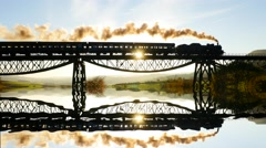 Steam engine locomotive crossing bridge at sunset. mirror reflection silhouette Stock Footage