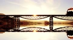 Romantic scene of nostalgic locomotive crossing bridge reflecting in water lake Stock Footage