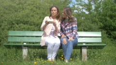 Two young women sitting on a park bench talking Stock Footage