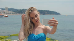Summer beach vacation girl taking fun mobile selfie photo with smartphone. Cute - stock footage