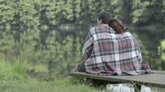 Young romantic couple in nature seated on lake jetty look at panorama Stock Footage
